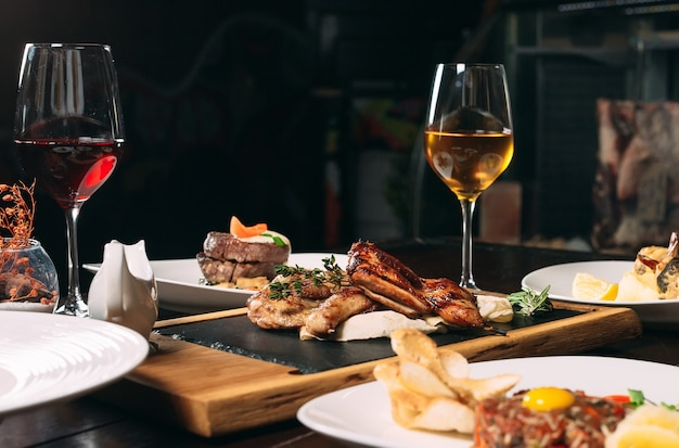 ヤマウズラのグリル、スズキ、タルタルス。レストランのテーブルでさまざまな料理。