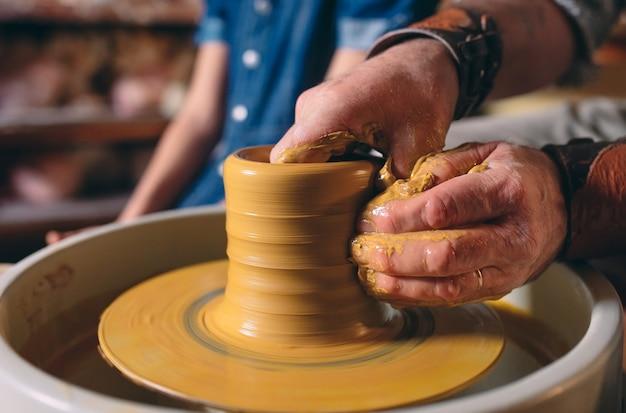 Гончарная мастерская. дедушка учит внучку гончарному делу. глиняное моделирование