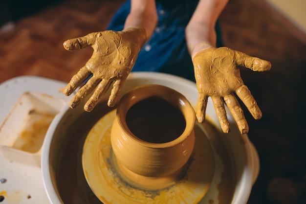 Гончарная мастерская. маленькая девочка делает вазу из глины. глиняное моделирование