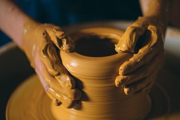 陶器のワークショップ。小さな女の子が粘土の花瓶を作ります。粘土モデリング
