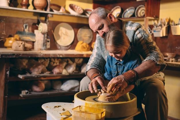 陶器のワークショップ。おじいちゃんは孫娘の陶器を教えています。粘土モデリング