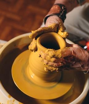 陶器のワークショップ。年配の男性が粘土の花瓶を作ります。粘土モデリング
