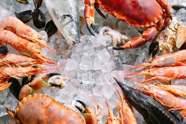 氷の上のシーフード。カニ、チョウザメ、貝、エビ、ラパナ、ドラド、白い氷の上。