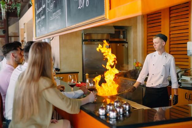 Шеф-повар готовит еду перед посетителями в ресторане