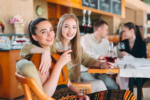 友達はレストランでワインを飲み、話して、笑って楽しんでいます。