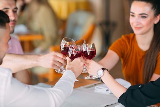 Друзья пьют вино на террасе ресторана.