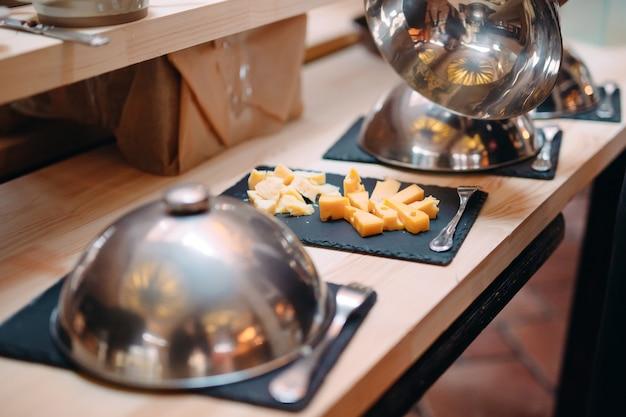 キャップ付きの金属製ボウルでチーズを切る。ホテルまたはレストランでの朝食。