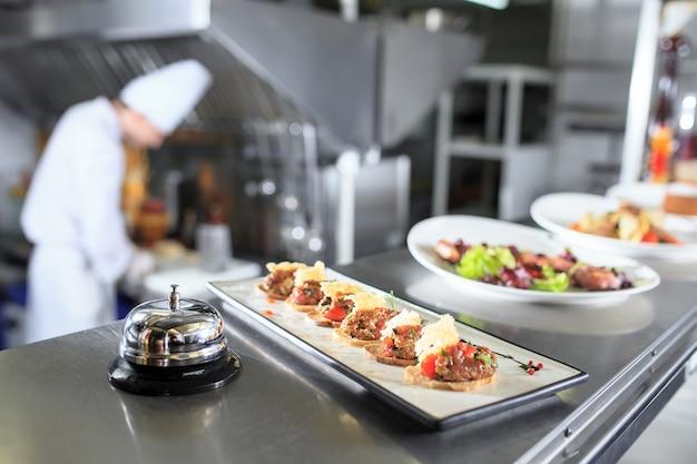 Распределительный стол на кухне ресторана. шеф-повар готовит еду