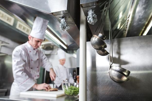 まな板でシェフが肉を切る、プロの料理人がレストランでナイフと肉を切る