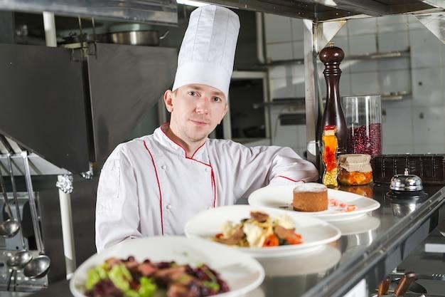 レストランのキッチンで調理された食品とシェフの肖像画。