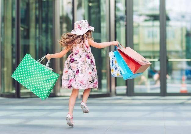 ショッピングでかわいい女の子。買い物袋を持つ子供の肖像画。ショッピング。女の子。
