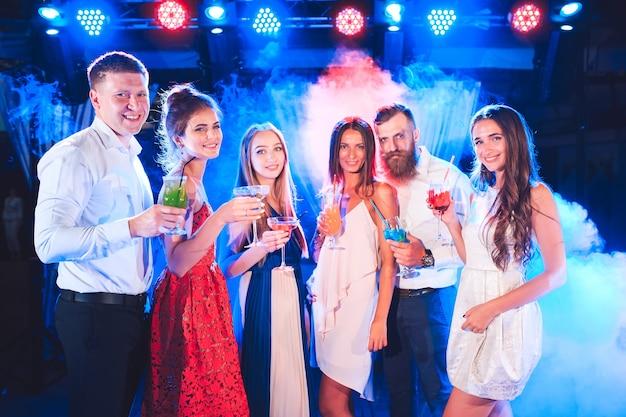 Друзья с коктейлями пьют на вечеринке.
