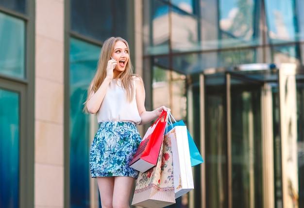 ライフスタイルの肖像若いブロンドの女の子、買い物袋が店から出て、携帯電話で話しています。