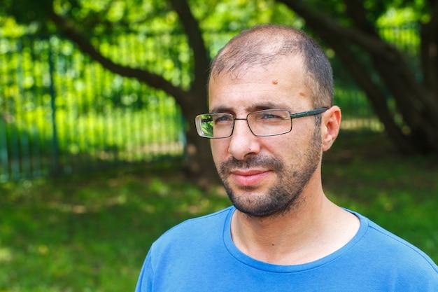 悪い視力と脱毛を持つ若い男の肖像。