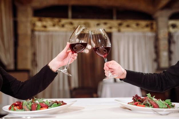 Мужчина и женщина пьют красное вино. на снимке крупным планом руки в очках.