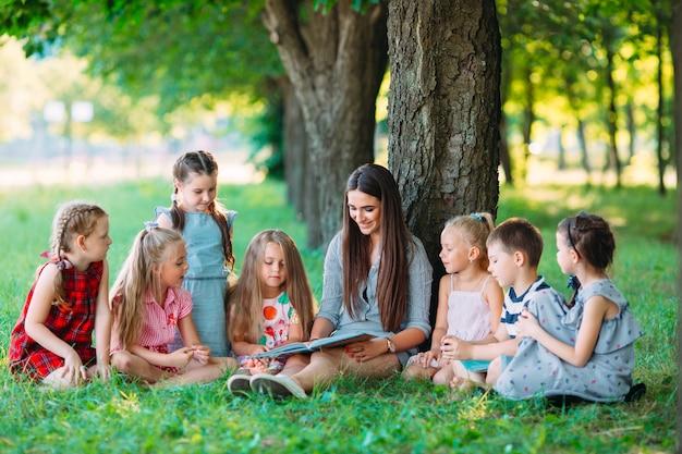 Дети и образование, молодая женщина на работе в качестве педагога, чтение книги для мальчиков и девочек в парке.