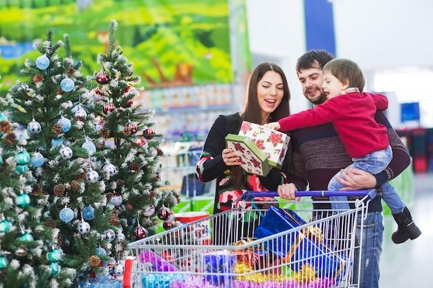 Счастливая молодая семья в супермаркете выбирает подарки на новый год.