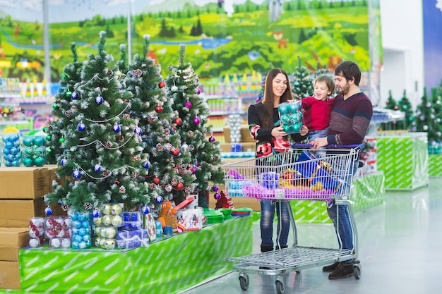 スーパーマーケットで幸せな若い家族は、新年の贈り物を選択します。