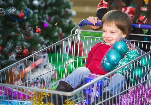 Новогодний шоппинг. ребенок делает покупки в супермаркете со своим родителем.