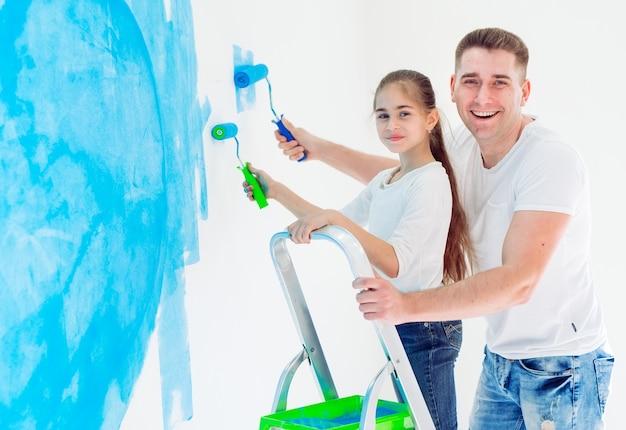 Отец и его маленькая дочь крася стену в новом доме.