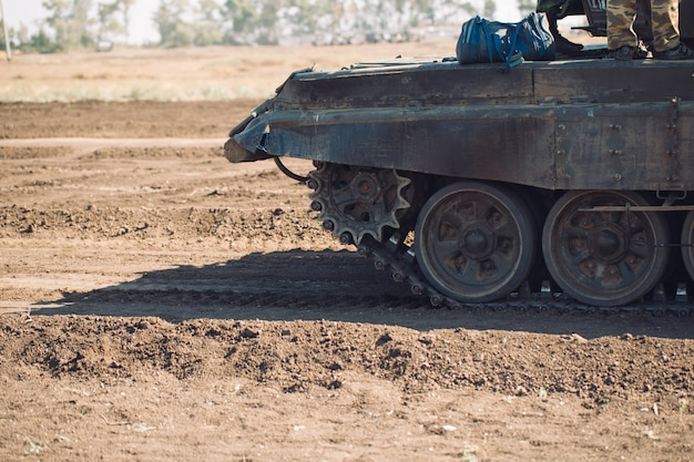 Бронированный танк едет по бездорожью. танковые учения в деревне.