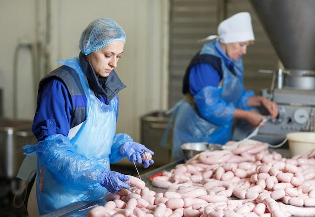 Мясники, перерабатывающие колбасы на мясокомбинате.