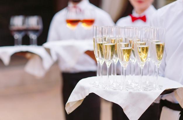 ウェイターはお客様にアルコール飲料をお迎えします。トレイにシャンパン、赤ワイン、白ワイン。