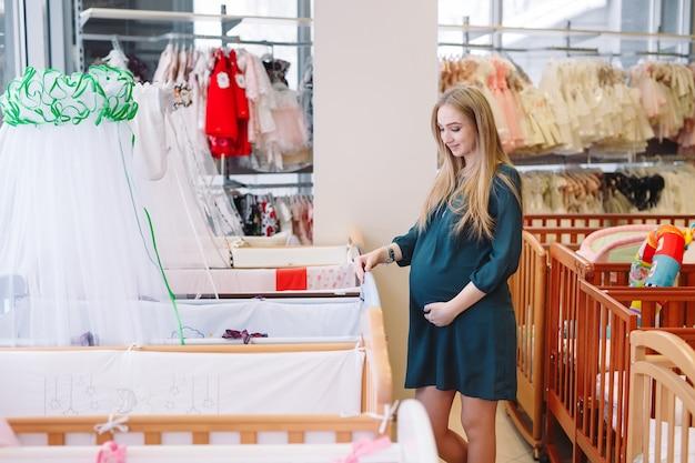 Беременная женщина выбирает детскую кроватку в магазине.