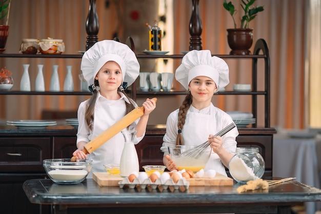 Смешные девчонки, дети готовят тесто на кухне.