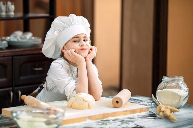 Девочка малыш готовит тесто на кухне.