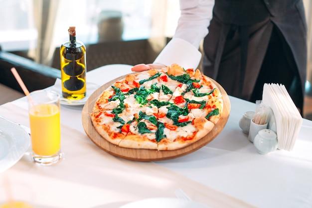 ウェイターはレストランのテーブルにピザを置きます。