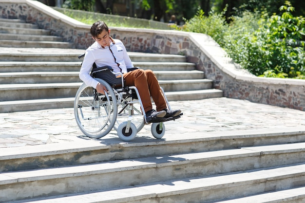 Молодой человек в инвалидной коляске, который не может спуститься по лестнице.