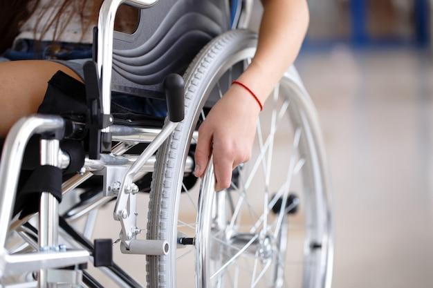 車椅子の少女が病院の廊下に立っています。