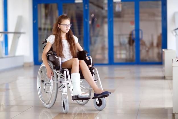 Молодая девушка в инвалидной коляске стоит в коридоре больницы.