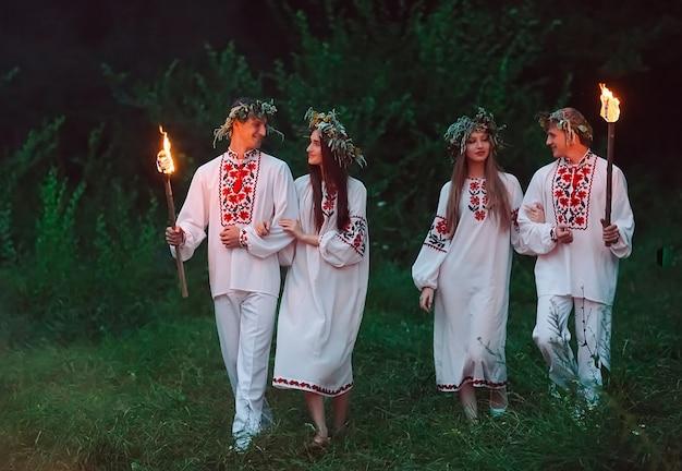 真夏、同じスラブの衣装を着た若者たちが火で松明を持っています。