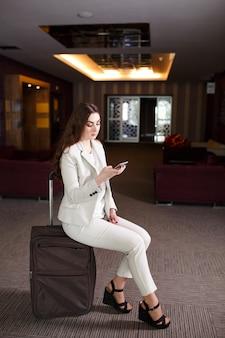 ターミナルや駅のスーツケースに座っている肖像若い女性、旅行で会った女性。