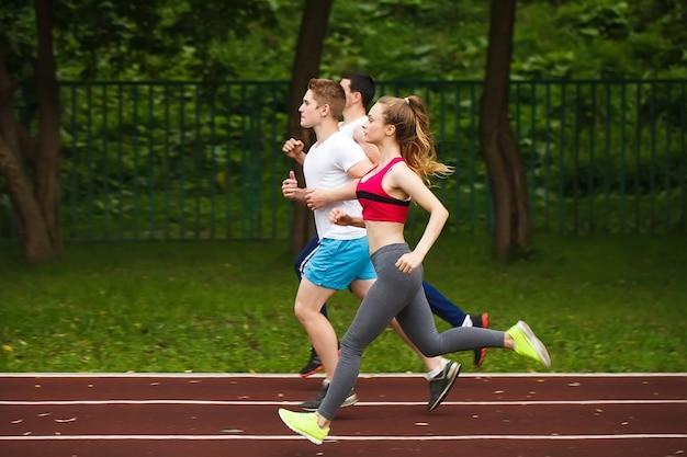 Бегут спортсмены на стадионе.