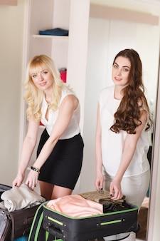 Две подружки собирают чемодан в гостиничном номере.