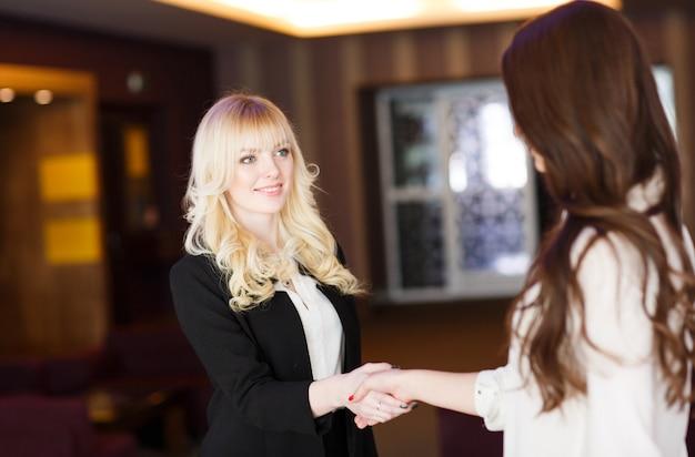 Две деловые женщины пожимают друг другу руки в современном офисе