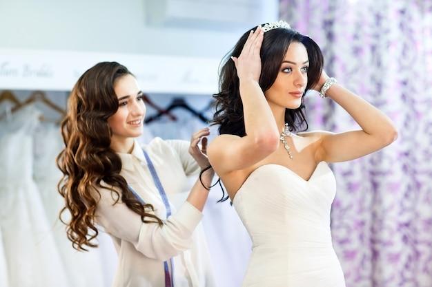 Женщина примеряет свадебное платье в магазине с ассистентом женщины.