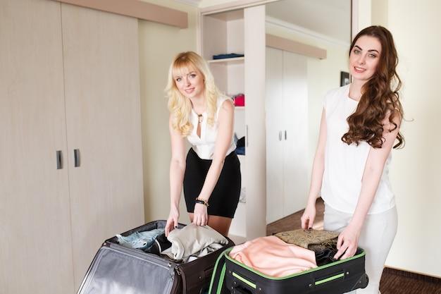 女性はホテルの部屋でスーツケースを収集します。