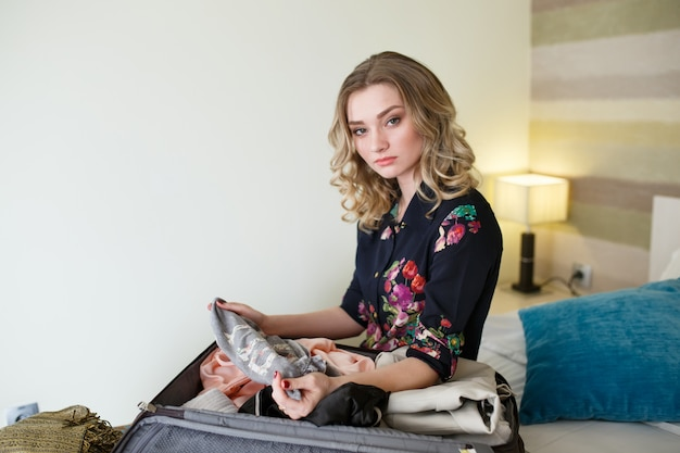 女の子は服をスーツケースに集めます。