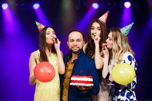 誕生日おめでとう!笑顔の友人のグループがケーキと一緒に集まった。