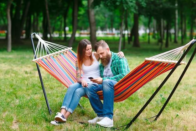 ハンモックの上に座って携帯電話と若いカップル