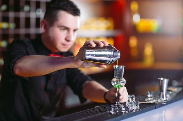 Бармен наливает свежий коктейль в бокал