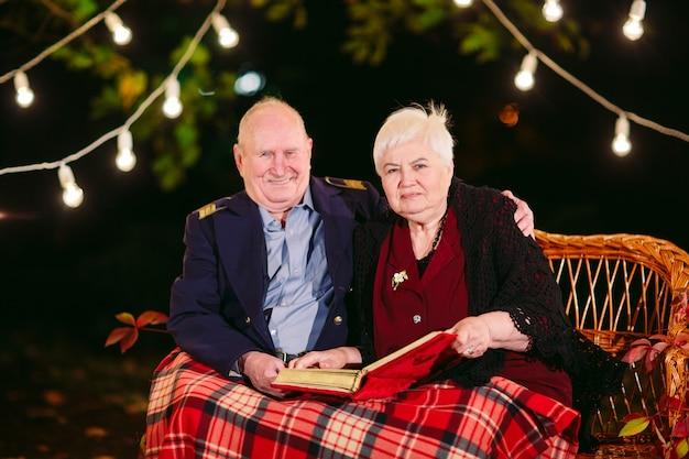 Счастливые воспоминания. счастливые старшие пары сидя на софе наблюдая альбом с фото.