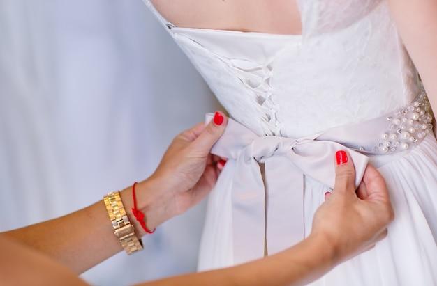 女性アシスタントの店でウェディングドレスを試着する女性。