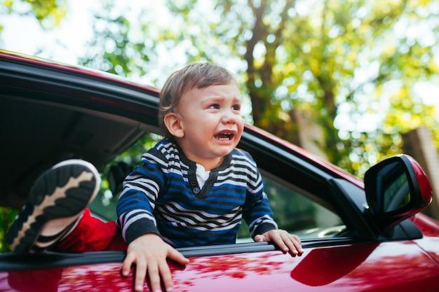 車の中で泣いている男の子。