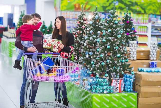 スーパーマーケットで幸せな若い家族がクリスマスの贈り物を選ぶ
