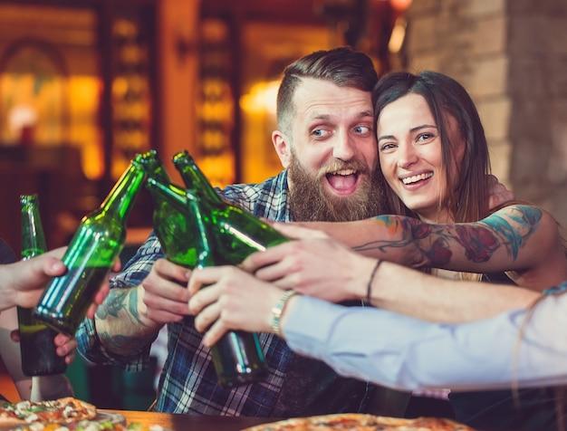 Друзья выпивают в баре, сидят за деревянным столом с пивом и пиццей.